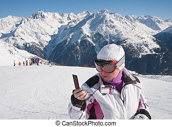 Skier in the mountains with a mobile phone in his hand