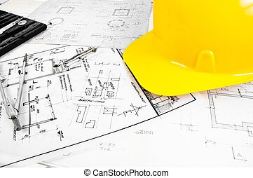 Angle shot of some construction plans and a yellow helmet