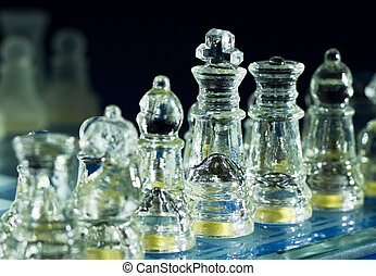awaiting orders - The clear glass chess pieces under direct...