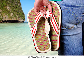 Vacations Start - Girl holding sandals on the first day of...