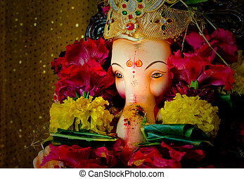 Lord Ganesh covered with religious flowers and spices
