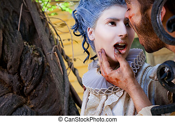 Male vampire touching ypung womans lips - Close-up of...