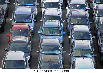 Many cars parked in a parking. Vehicles distributed in rows