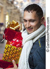 Young adult man with christmas gifts - Young adult handsome...