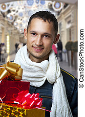 Young handsome man with christmas gifts - Young adult...