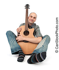 man sits with a guitar