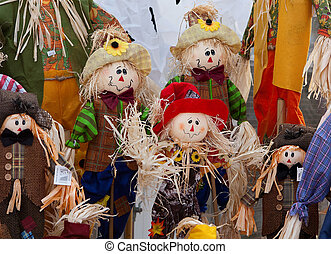 Smiling handmade cloth scarecrow dolls displayed together.