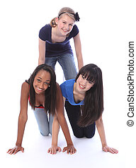 Mixed race teenage girl friends in fun pyramid - Human...