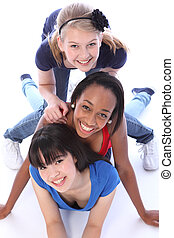 Three mixed race girl friends having fun together - Playful...