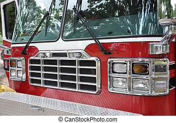Firetruck - closeup of the front of a fire truck with trees...