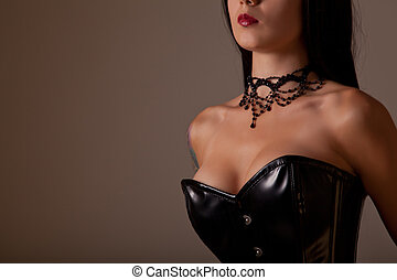 Close-up shot of busty woman in black corset, studio shot on...