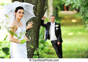 groom and bride with umbrella walking in park