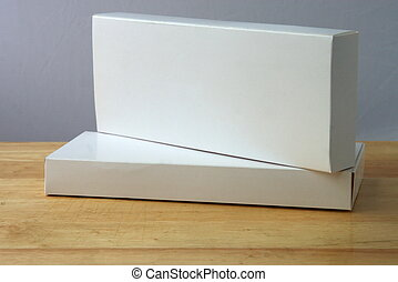 two white boxes - two white oblong boxes on a table