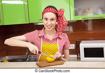 Woman in the kitchen with knife and lemon - Woman in the...