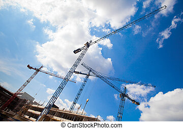 construction cranes and unfinished house against the blue...