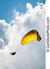 Yellow parachute against sky and clouds - Parachuter with...