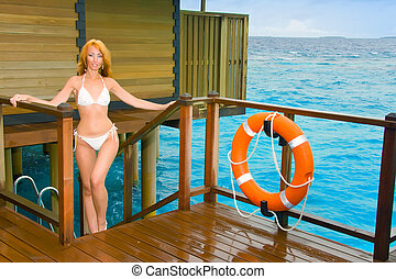 Young pretty woman stands in bathing suit on platform at villa on water, Maldives