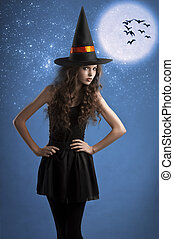 sweet halloween witch posing under the stars - very young...