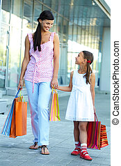 Shopping with mother - Portrait of a woman and girl walking...