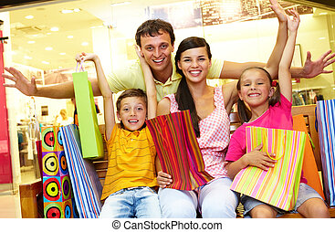 After shopping - Portrait of joyful family sitting in store...