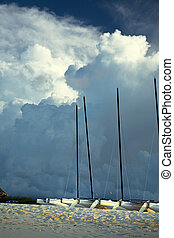 storm clouds - Recreational boats landed on the shore over...