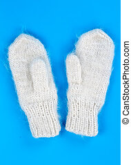 a pair of knitted wool mittens on a blue background