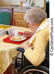 Old woman eating lunch in handicap chair