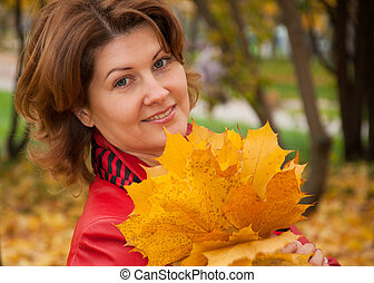 Woman in autumn park with a bouquet of maple leaves