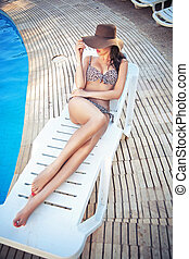 Attractive lady relaxing on swimming pool