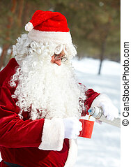 Santa in the forest - Santa Claus drinking hot tea in winter...
