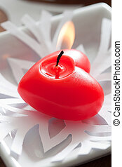 Red heart candle on white paper snowflake
