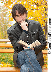 Middle-aged man with a book in autumn park