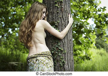 Portrait of romantic woman at the green forest