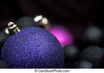 Unusual purple Christmas decorations against black...