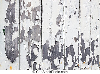 White flaky paint on a old weathered wooden fence.