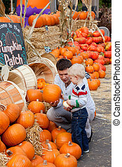 family at the pumpkin patch - happy father and son at the...