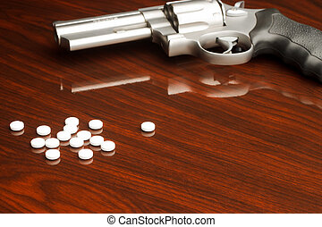 Pills Revolver - .357 revolver laying on wooden surface with...