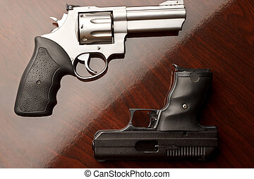 Revolver Vs Handgun - Revolver on surface with 9 mm handgun