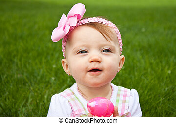 Easter Baby Hold Egg Close - Adorable baby holding a pink...