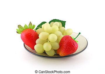Strawberries and bunch of grapes on the saucer