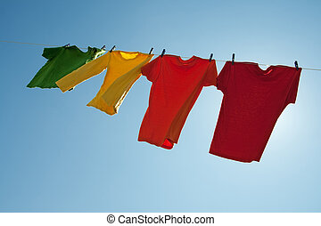 Colorful clothes hanging to dry in the blue sky, on a sunny...