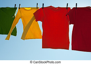 Bright multi-colored clothes drying in the wind, on a sunny...