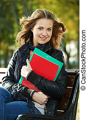 Student Girl sitting on bench outdoors