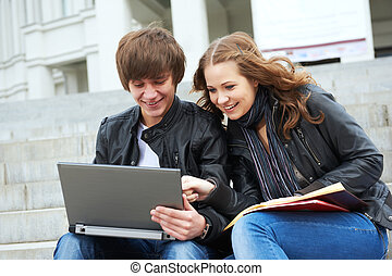 Two smiling young students outdoors
