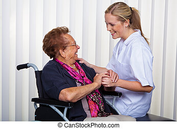 old woman in a wheelchair and a nurse - a nurse and an old...