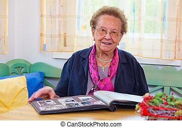 seniors leafs through a photo album - a senior puts on a...