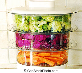 Colorful vegetables in steamer - green broccoli, magenta...