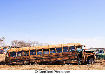 Junk Yard Bus - Old rusty school bus partly collapsed in...