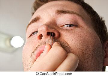 Man Close Nose Hair Pluck - Man pucking nose hair with...