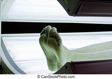 Tanning Bed Feet - Bare feet and legs in lit tanning bed